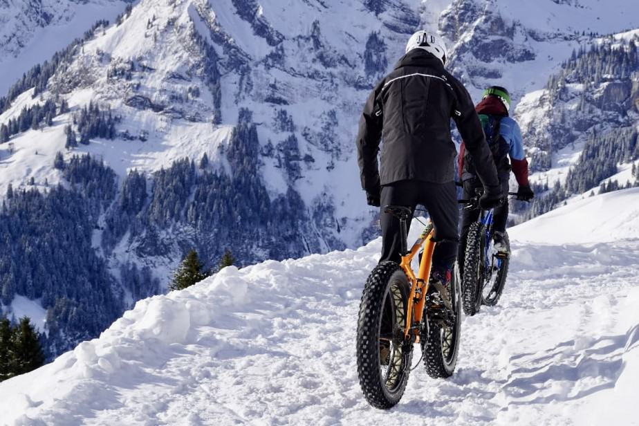 Two cyclists cycling in the snow