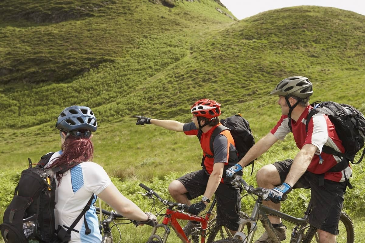 Three cyclists wearing helmets in the countryside
