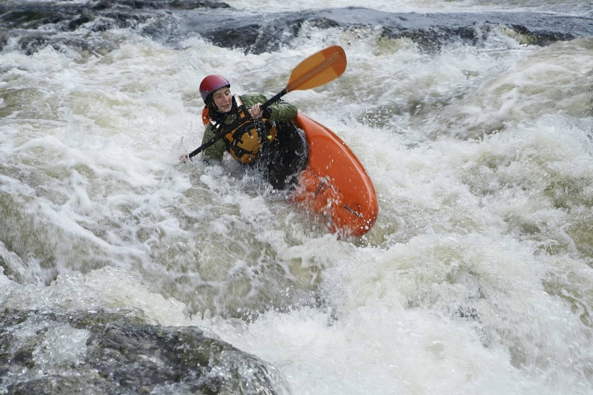 Kayak tipping over in rapids