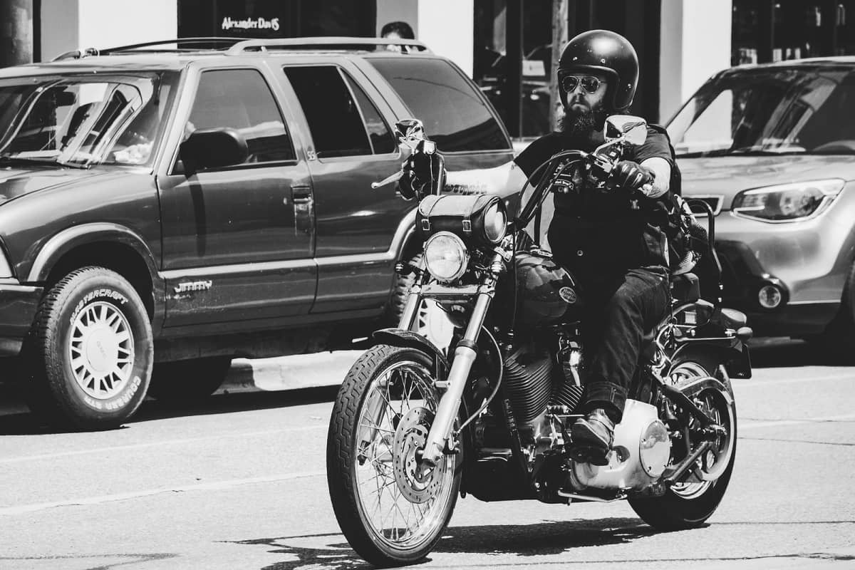 Bearded guy riding Harley Davidson motorcycle in city