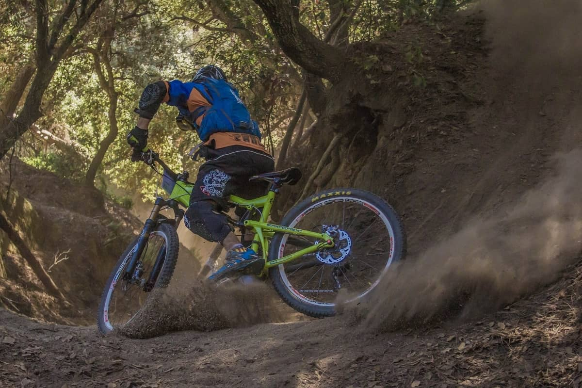 MTB rider kicking up some dirt on a country trail