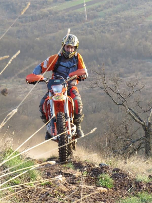 Man riding red dirt bike on country trail