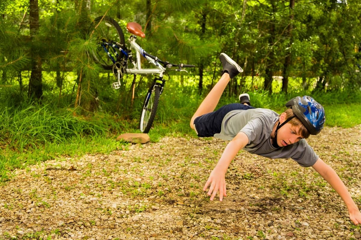 Boy flying through the air after hitting rock with bicycle