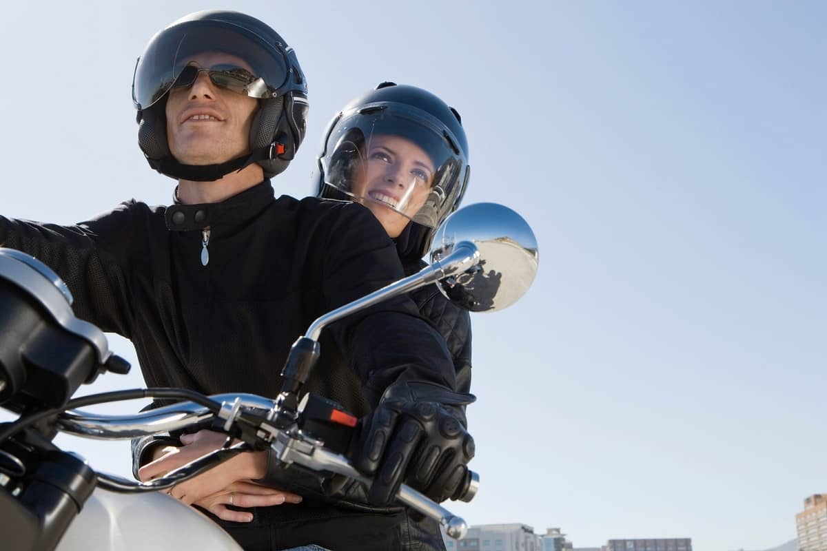 Couple riding motorcycle wearing helmets