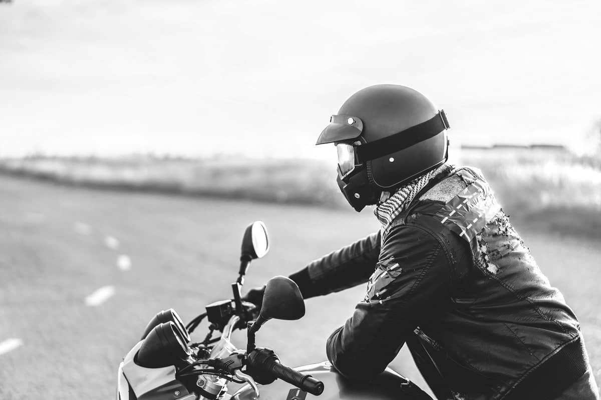 Motorcyclist wearing peaked helmet with goggles