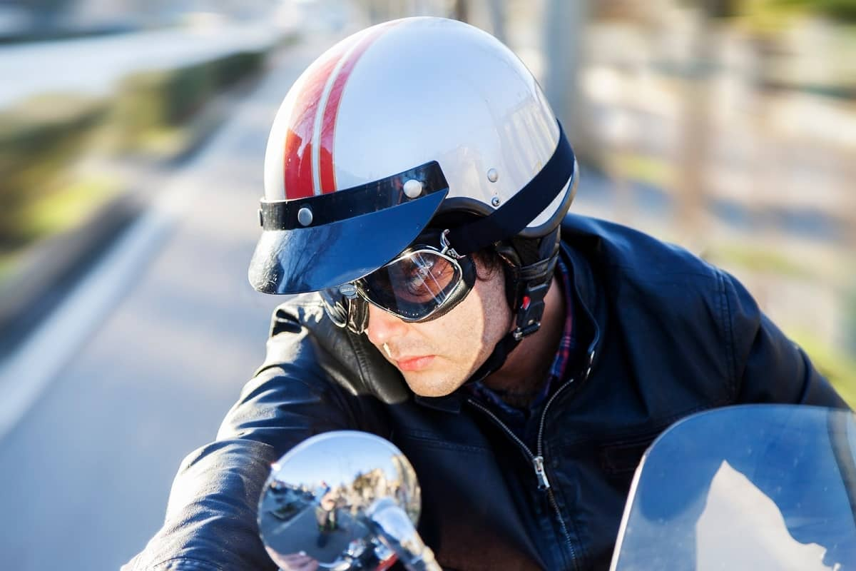 Young person wearing peaked helmet on motorcycle