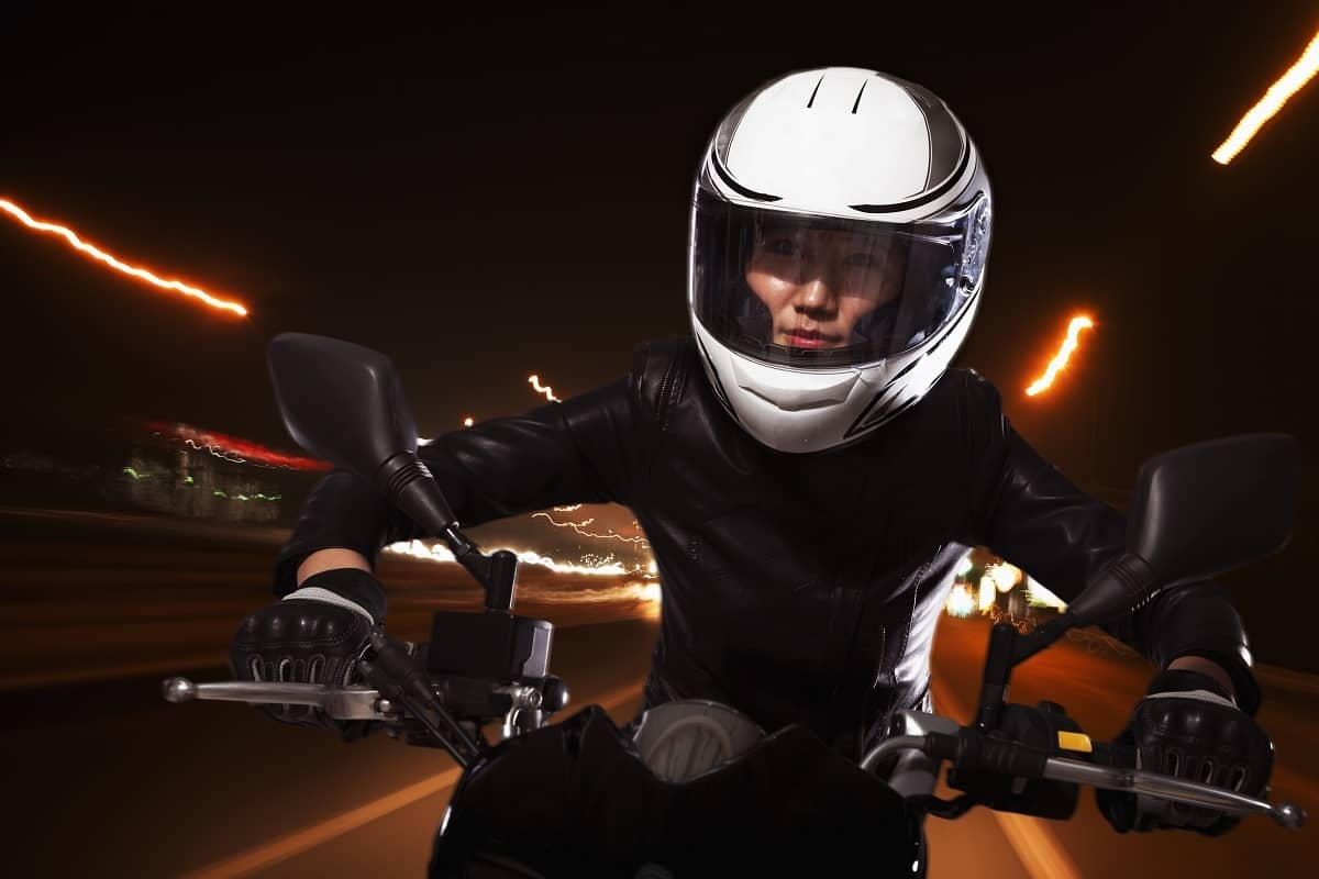 Woman riding motorcycle at night in city