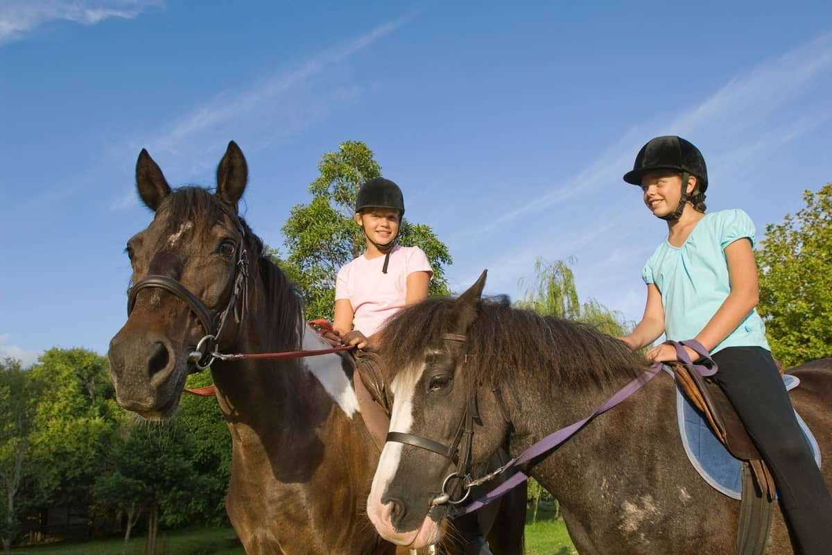 Two pre-teen girls riding horses