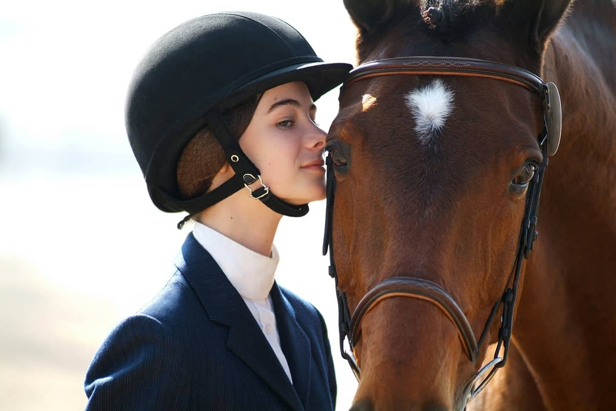 Girl about to kiss horses head