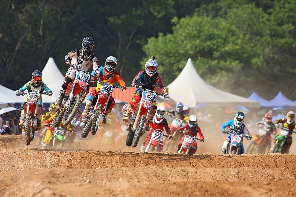 Many motocross racers racing on dirt track