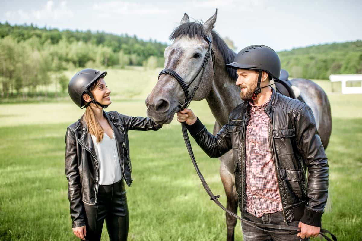 Man and woman wearing helmets standing with horse.