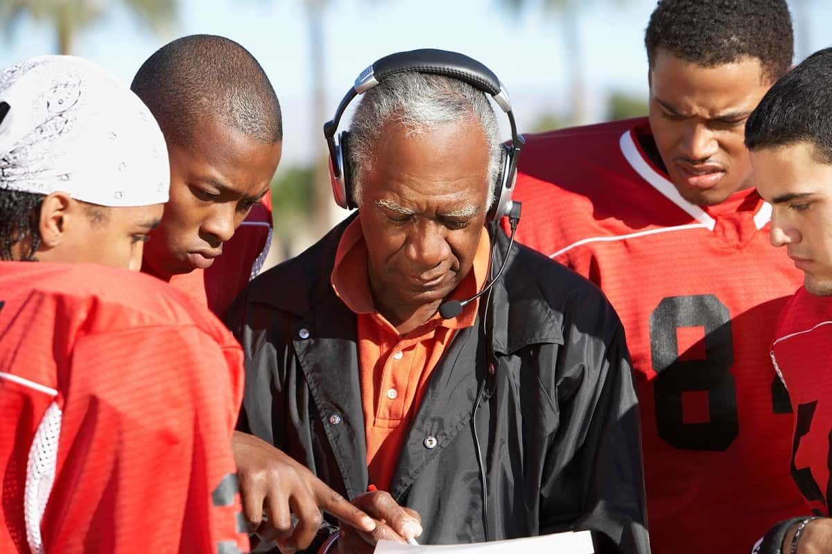 Football coach discussing strategy with his players