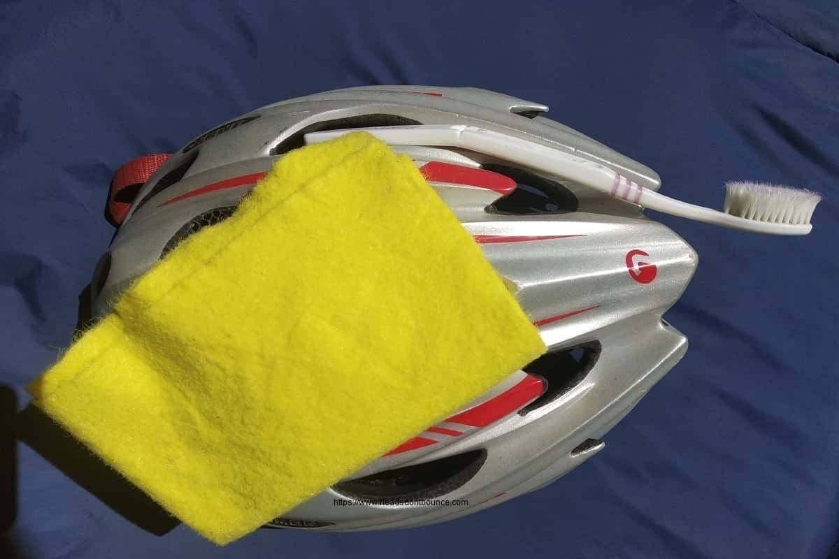 Grey and red helmet with yellow wash cloth and toothbrush on blue background