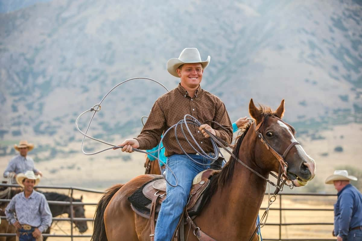 Young man wearing cowboy hat and twirling lasso riding brown horse.
