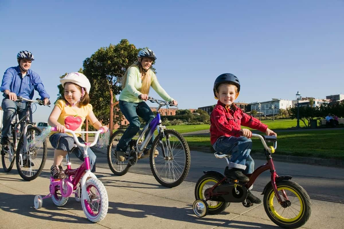 Man and woman with 2 kids riding together wearing cycling helmets